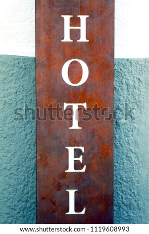 """Lettering """"Hotel"""" on a blue-grey-white wall"""
