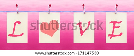 Letters hanging from a clothes line spelling Love with a heart - stock photo