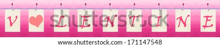 Letters hanging from a clothes line spelling Valentine with a heart - stock photo