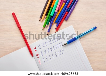 letters in a notebook and pencils