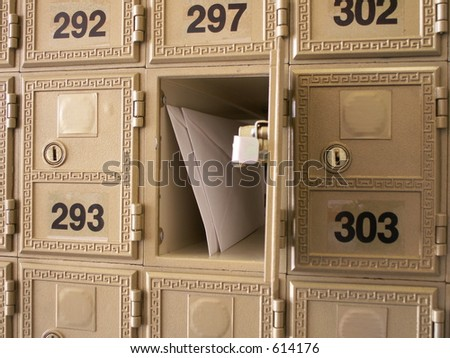 letters in an open mailbox in a wall of mailboxes