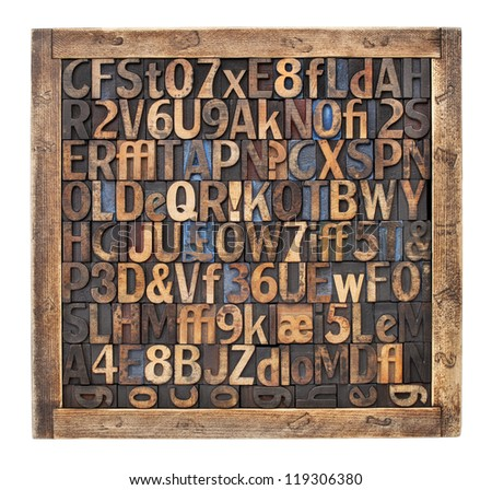 letters, numbers, punctuation symbols in vintage letterpress wood type blocks placed randomly in a wooden box - stock photo