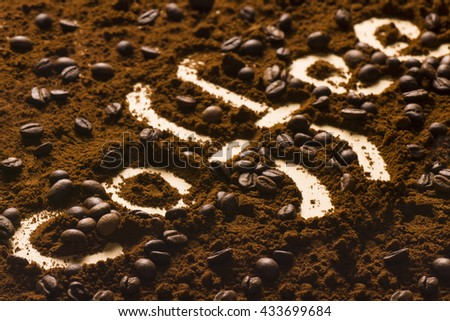 Letters of coffee are written from coffee powder and beans.