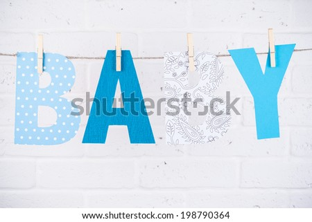 letters of word baby hanging on clothesline against white brick wall - stock photo