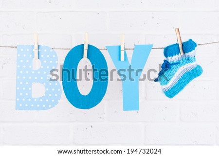letters of word boy and knitted socks hanging on clothesline against white brick wall - stock photo