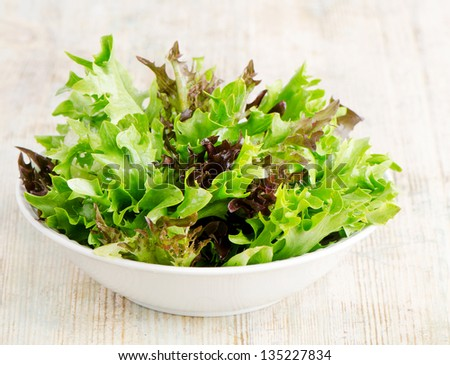 Lettuce salad mix on a wooden table - stock photo