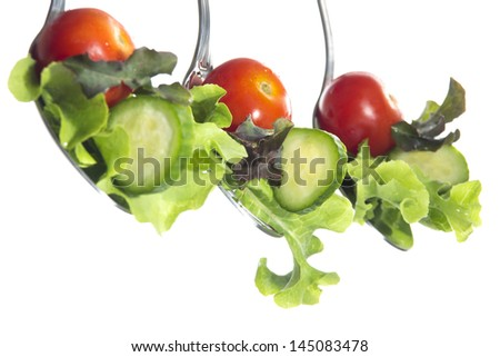 Lettuce, slices of cucumber and tomato sherry in steel shiny spoons on a white background - stock photo