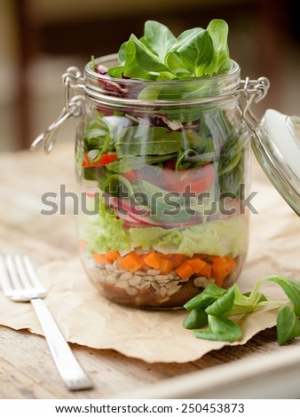 Lettuce, tomato and other vegetables in glass jar