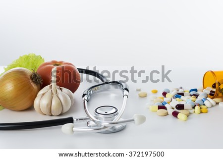 Lettuce, tomato, garlic and onion, near a stethoscope and a large amount of drugs spread around in a white background.