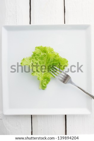 Lettuce with a fork on a plate - stock photo