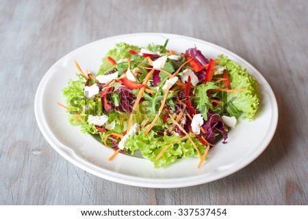lettuce with slices of carrots, peppers, arugula , cheese