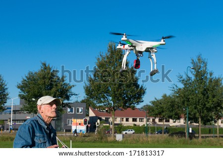 LEUSDEN, NETHERLANDS - SEPTEMBER 28: Senior man controlling a small quadrocopter for taking pictures from above on september 28, 2013 in Leusden, netherlands