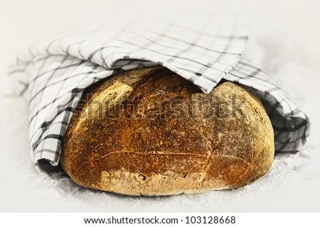 Levain bread on flour powder, uncut - stock photo