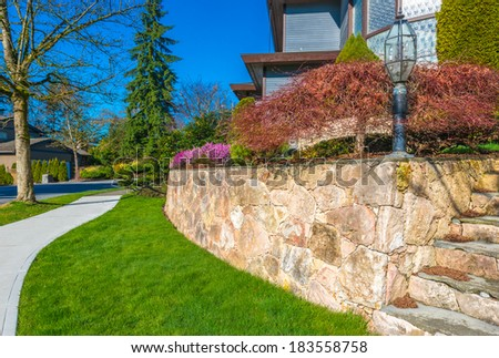Leveled and stoned curved front yard with some flowers and nicely trimmed bushes and grass. Landscape design. - stock photo