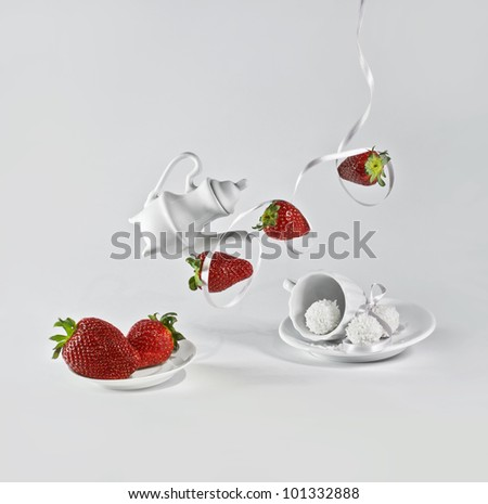 Levitating strawberry with white ribbon and small decorative dishes. - stock photo