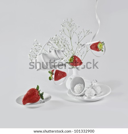 Levitating strawberry with white ribbon, little flowers and small decorative dishes. - stock photo