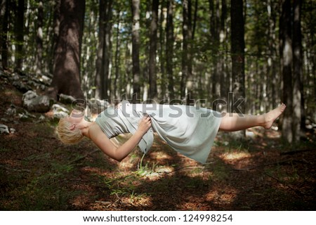 Levitating woman in the forest - stock photo