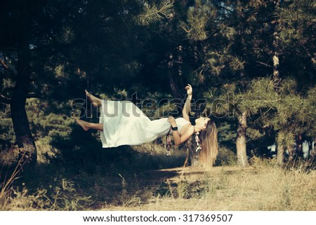levitation girl with white dress in the forest