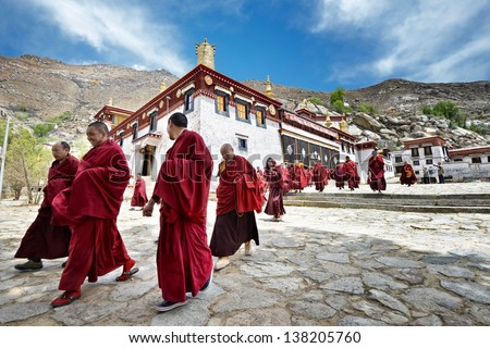 LHASA - MAY 1: monks leave the main assembly hall of  Sera monastery on May 1, 2013 in Lhasa. The main assembly hall is the venue for religious chanting - part of the religious curriculum. - stock photo