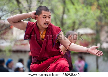 LHASA - MAY 1: Unidentified monk debates at Sera monastery on May 1, 2013 in Lhasa, Tibet. Debating is part of the monastery curriculum and those who do well have chance to become a higher lama. - stock photo