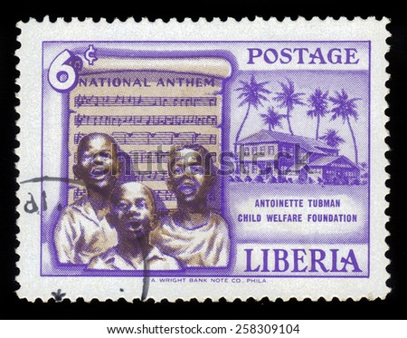 LIBERIA - CIRCA 1957: a stamp printed in the Liberia shows children sing the national anthem, founding of the Antoinette Tubman child welfare foundation, circa 1957 - stock photo