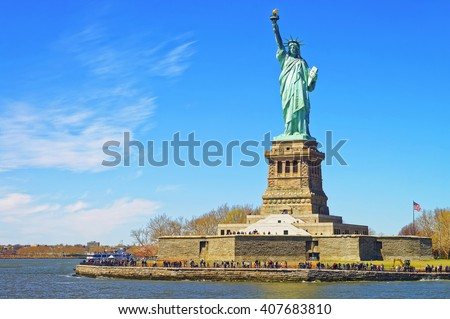 Liberty Island and Statue in Upper Bay, New York City, USA. In Upper New York Bay. Tourists are walking on the island. - stock photo