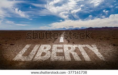 Liberty written on desert road - stock photo