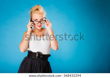 Librarian, accountant and secretary concept. Retro, pin up style. Young blonde woman in glasses. Girl holding smartphone on blue background in studio. - stock photo