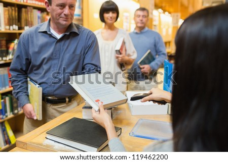 Librarian handing book to man at library desk - stock photo