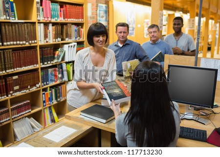 Librarian handing book to woman at library desk - stock photo