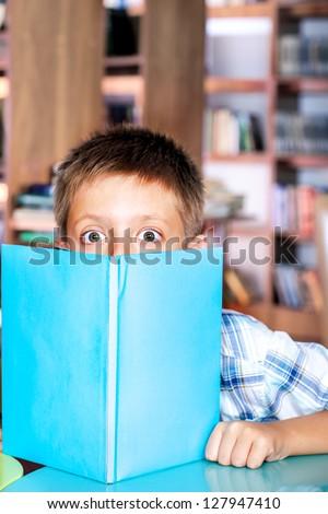 Library: amazed boy hiding behind book - stock photo