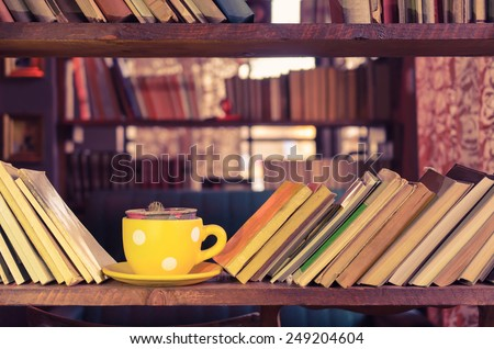 Library bookshelf and yellow cup - Old fashioned style - stock photo