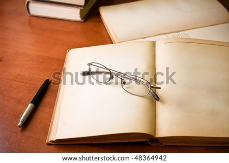 library desk with books, glasses and pen - stock photo