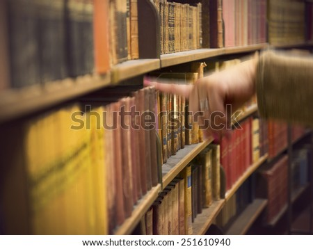 Library or book store with rows of old antique books, and a hand of a woman reaching for a book - stock photo