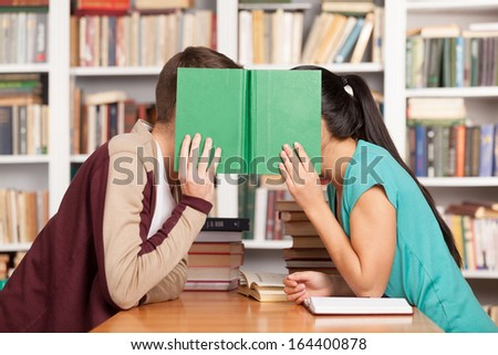 Library romance. Young man and woman sitting close to each other at the library desk and hiding their faces behind a book - stock photo