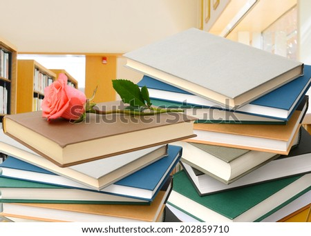 library with stack of books and rose gift - stock photo