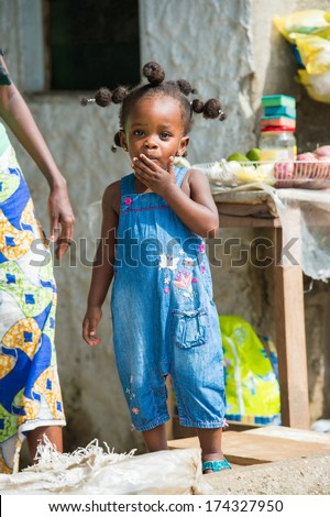 LIBREVILLE, GABON - MAR 6, 2013: Unidentified Gabonese little girl in the street in Gabon, Mar 6, 2013. People of Gabon suffer of poverty due to the unstable economical situation