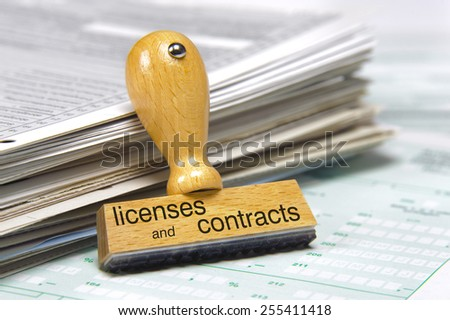 licenses and contracts printed on rubber stamp laying over documents - stock photo