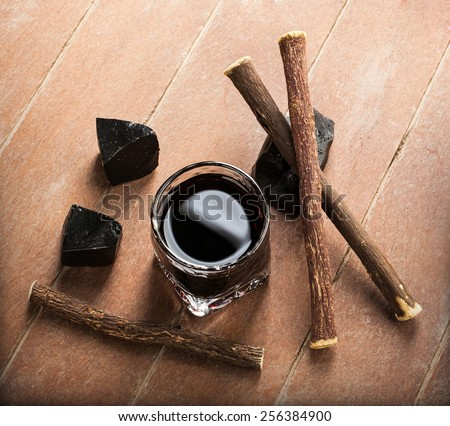 Licorice liqueur with pure blocks and roots on wooden table. - stock photo