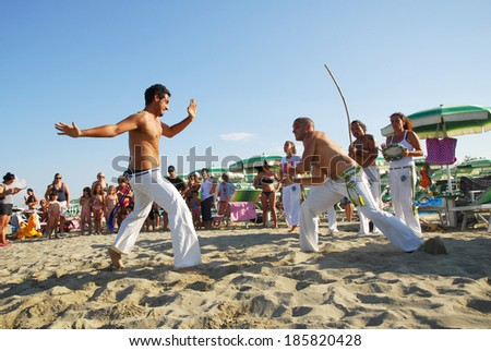 LIDO ADRIANO, RAVENNA, ITALY � JUNE 22, 2012: young Brazilians dancing capoeira on the public beach. More than 60000 tourists come on these beaches every year - stock photo