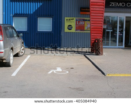 LIEPAJA, LATVIA - APRIL 11, 2016: Parking place with special symbol is reserved for disabled person car near supermarket entrance.        - stock photo