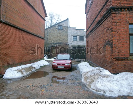 LIEPAJA, LATVIA - JANUARY 27, 2016: On thaw small bystreet has walls of dirty melting snow on both sides. - stock photo