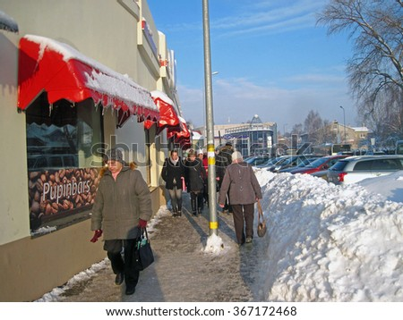 LIEPAJA, LATVIA - JANUARY 21, 2016: Sidewalks are covered vith slippery snow and have high snow banks along them. - stock photo