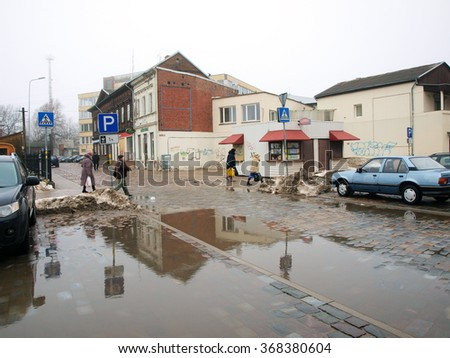 LIEPAJA, LATVIA - JANUARY 27, 2016: The thaw begins and big paddles are on street and car parking.        - stock photo