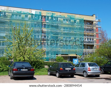 LIEPAJA, LATVIA - MAY 21, 2015: Workers are renewing multistory apartment house near car parking place.       - stock photo