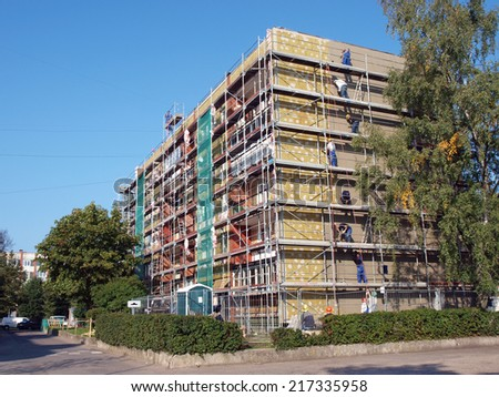 LIEPAJA, LATVIA - SEPTEMBER 11, 2014: Workers are heating apartment house with stone wool plates. - stock photo