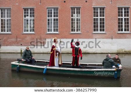 LIER, BELGIUM - NOVEMBER 14, 2015: Sinterklaas and Zwarte Piet waving from a traditional boat. - stock photo