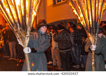 Liestal, Switzerland February 22, 2015: Chienbase parade and attendees in city of Liestal. Chienbase is the traditional Fasnach fire spectacle where burning carriers get pulled through the Town.