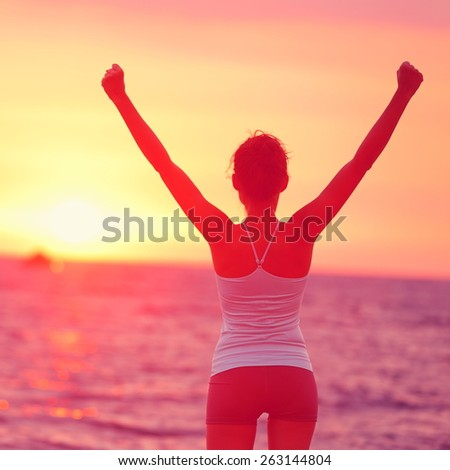 Life achievement - happy woman arms up in success. Back view of female silhouette proud of reaching her health goal arms raised looking at ocean and sunset. Happiness winning goal concept. - stock photo