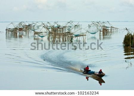 Life asian fisherman and bamboo machinery (square dip net)at canal. Klongyoun canal, Pattalung, Thailand - stock photo